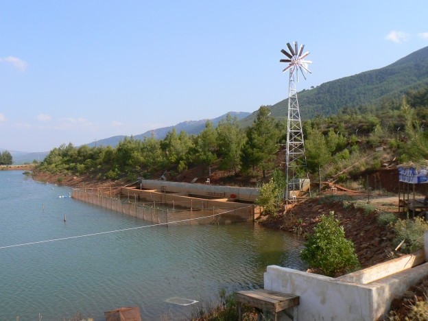 windmill on a hill above a sustainable seafood farm producing carp in Turkey